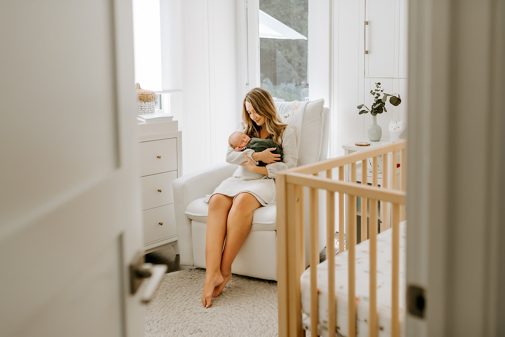 photo of mother in nursery, sitting down and holding her newborn son in her arms, white couch, wooden crib, natural light lifestyle newborn photographer for marin, newborn photographer, diana jex photography