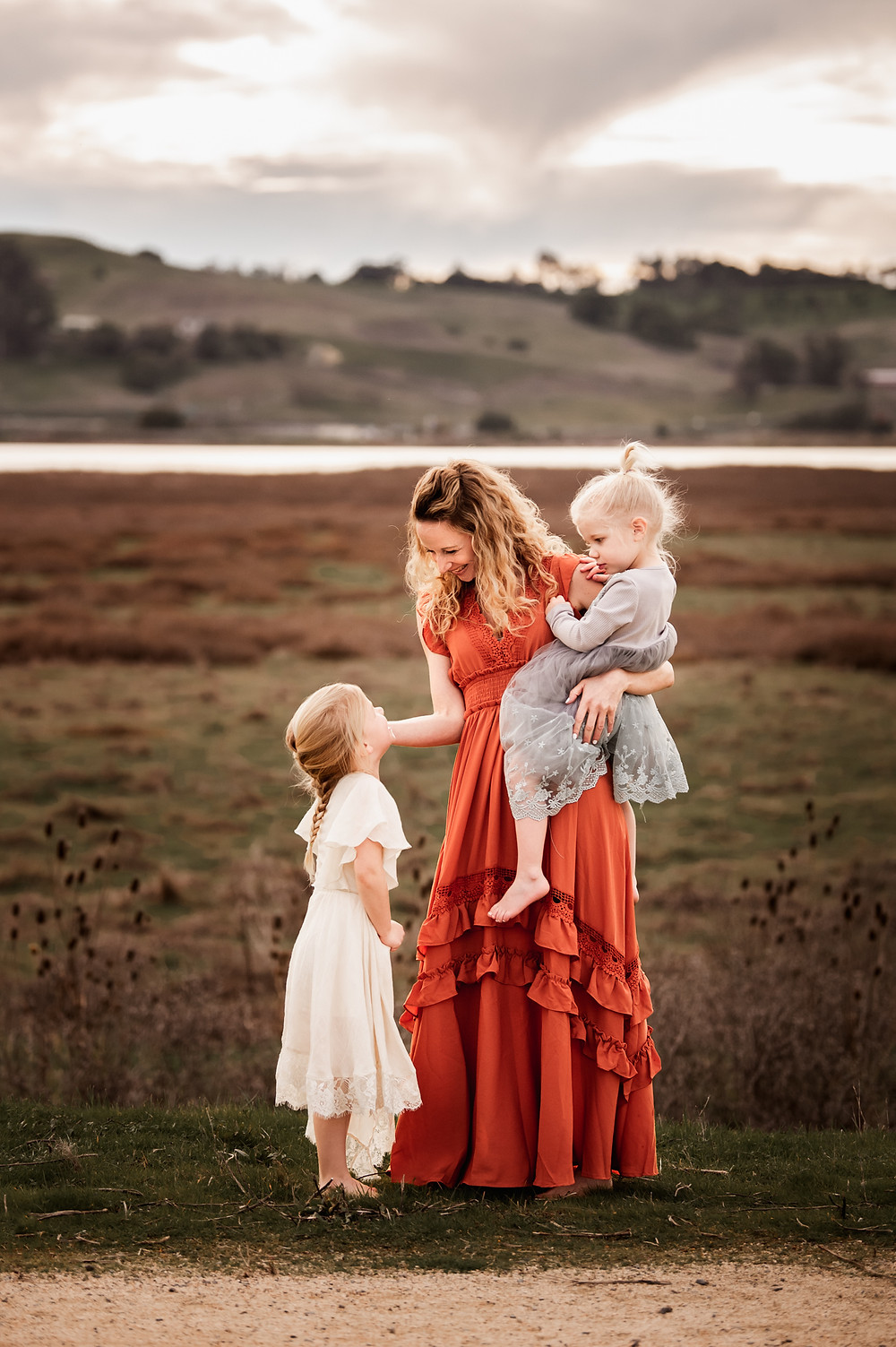 mom looking loving down at her daughter while holding the other daughter in her other arm, long red maxi dress, water in background, sunset, petaluma, Sonoma County family photographer for Sonoma County, Diana Jex Photography