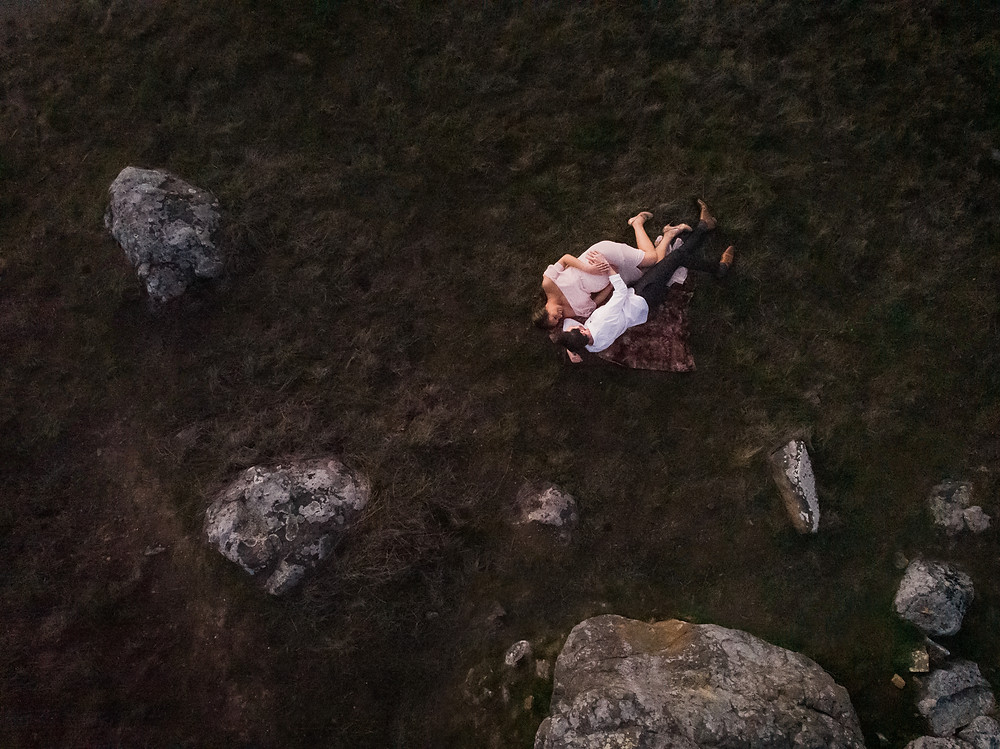 Drone photography, drone image of expecting couple lying down on a blanket embracing each other, rocks, golden hour, sunset, Sonoma, Marin, Napa family photographer for Sonoma County Diana Jex Photography