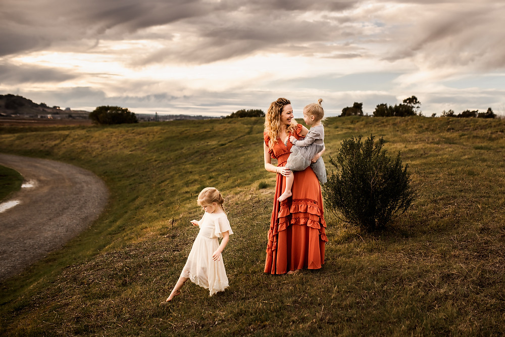 mom with her two daughters, one is walking back towards the trail and mom is holding up the other daughter, looking at her and smiling, open space preserve in petaluma, sunset motherhood session, family photographer for Sonoma County, Diana Jex Photography