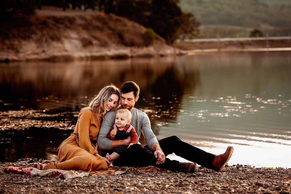 beautiful family of three sitting down by lake with sunset behind them, golden hour photography in Sonoma County, wine country, Petaluma, Santa Rosa, Napa, Family of three sitting laying down on blanket, photographed during golden hour, toddler son looking up at camera