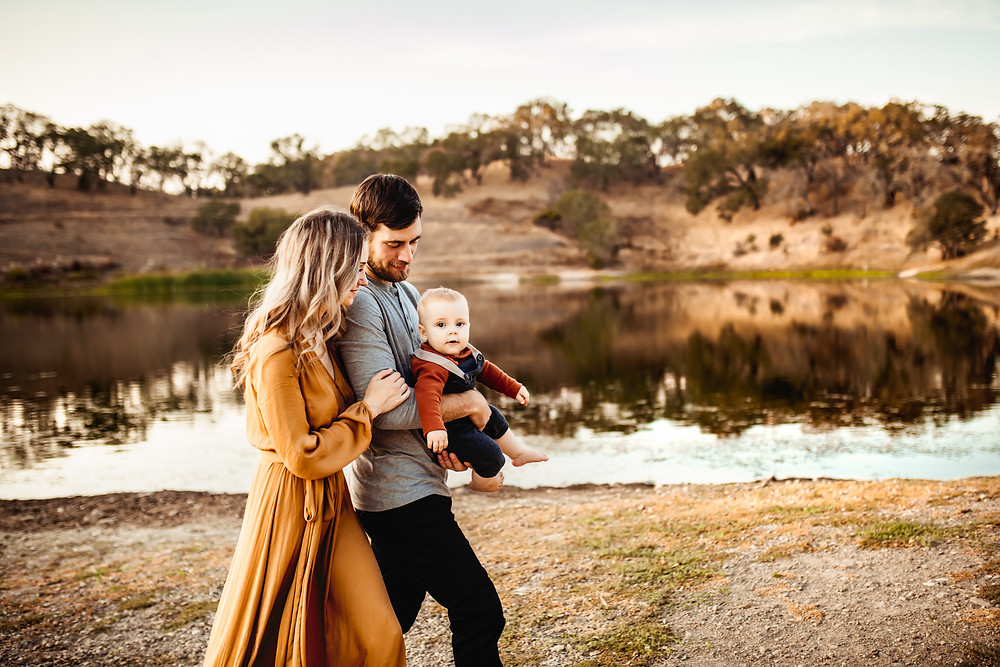 family of three walking together, dad holding baby boy, husband and wife, golden hour, lake in background with trees and rolling hills, toddler son looking at camera