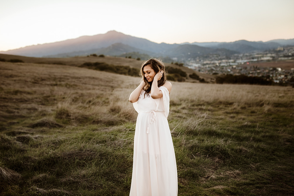 Expecting mother in long light pink maxi dress from Baltic Born, running her hands through her hair, sunset in background, mountains in background, Marin County, Tiburon, Sonoma, Marin, Napa family photographer for Sonoma County Diana Jex Photography