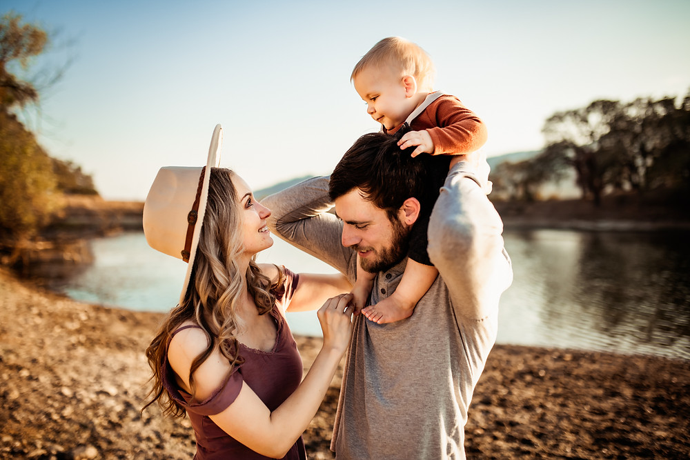 Best photo from family photo session in Sonoma County, water in background, baby boy and dad's shoulders, mom looking lovingly at her toddler son, family of three, golden hour, Glen Ellen, wine country