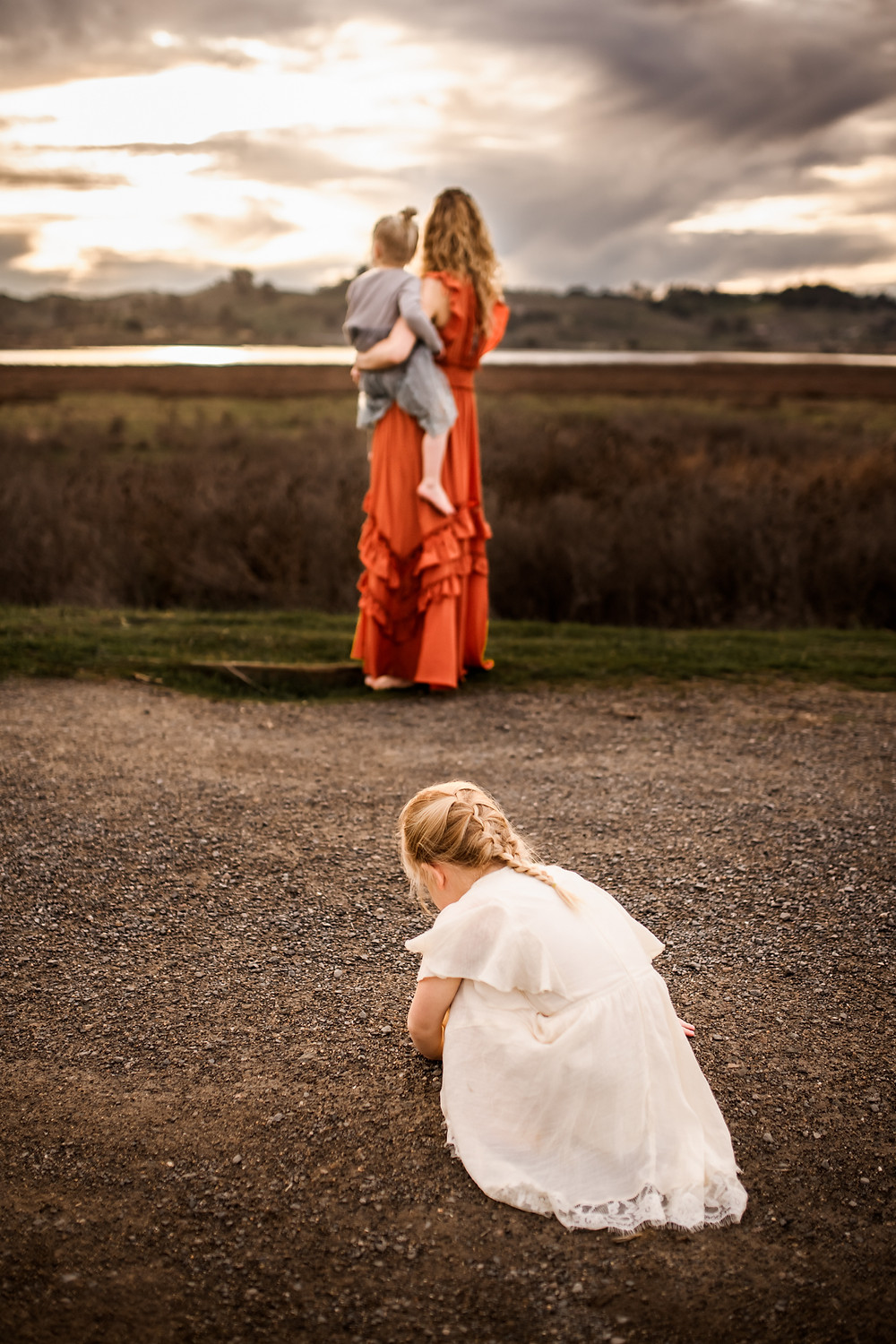 big sister playing in the dirt with mom and baby sister in the background, family photographer for Sonoma County, Diana Jex Photography
