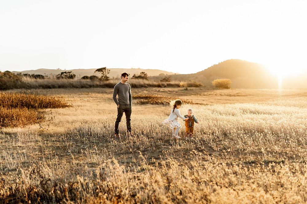 Sister holding on to baby brother's hand as he is learning to walk, dad looking at siblings in background, sunset with rolling hills in background, golden hour photographer, Northern California family photographer, Sonoma County family photographer, Diana Jex, Novato petaluma