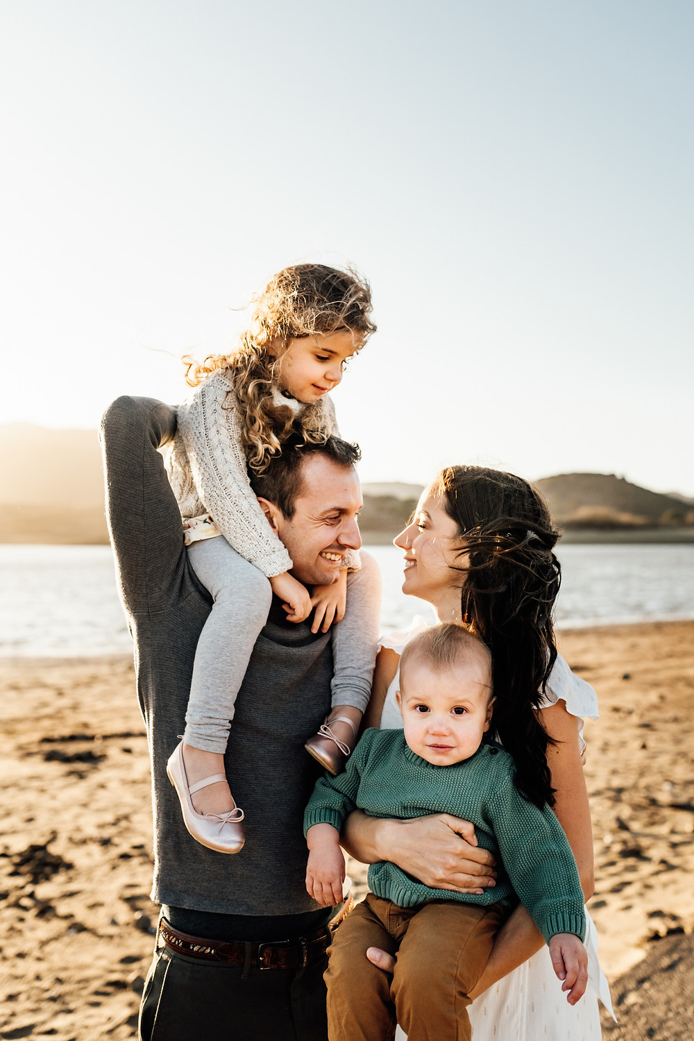 close up photograph of family, mom holding baby toddler boy, boy in green sweater, mom looking lovingly at dad, daughter on dad's shoulders, water, sunset, Novato, sunset family photographer, Northern California family photographer, Diana Jex