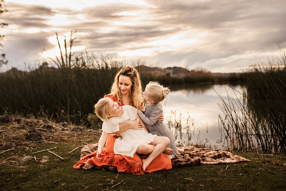 mother sitting down with both of her daughters, holding them, they are all laughing and cuddling together, big sister is laughing, water with cloud reflections in the background, dramatic skies, family photographer for Sonoma County, Diana Jex Photography