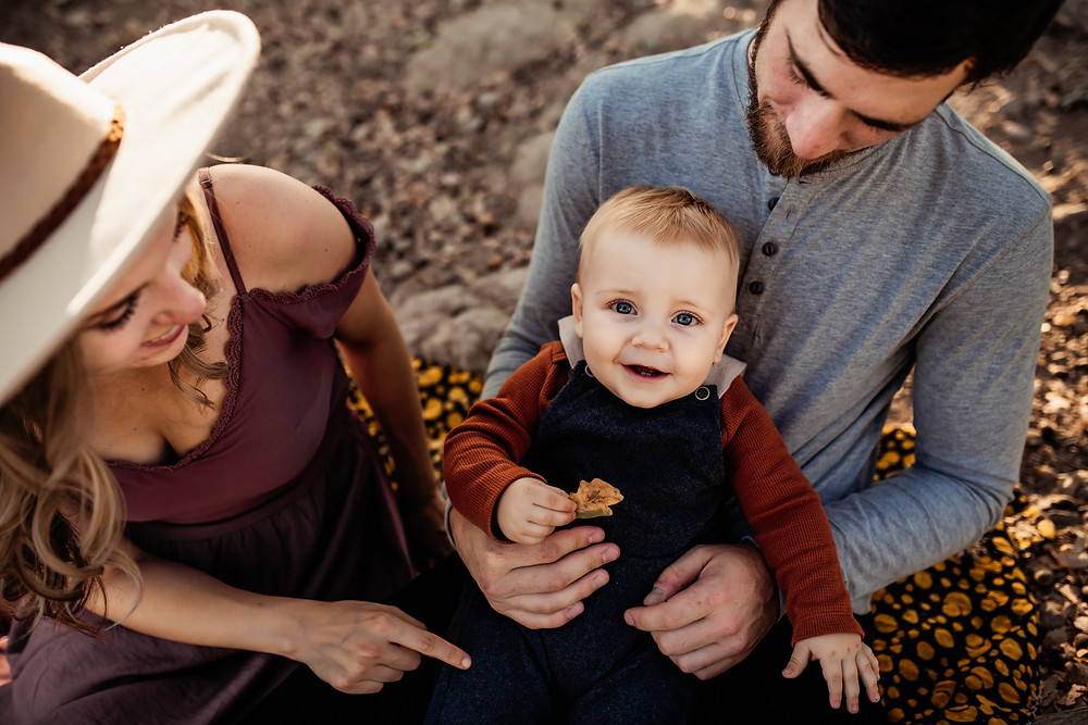 Family sitting down, outside on a nature path, baby boy looking up at camera holding a leaf, smiling