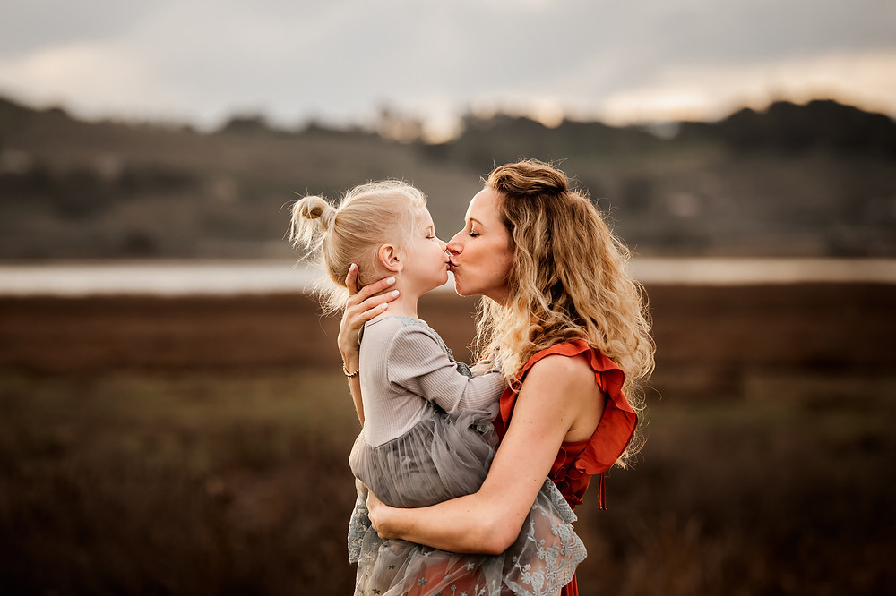 mother and daughter kissing each other, sunset and petaluma hills in the background, motherhood photo session in sonoma County, family photographer for Sonoma County, Diana Jex Photography