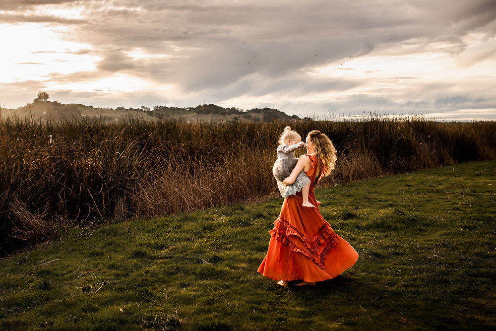 mom in long maxi burnt orange dress twirling around with her daughter in an open space preserve in petaluma, family photographer for Sonoma County, Diana Jex Photography