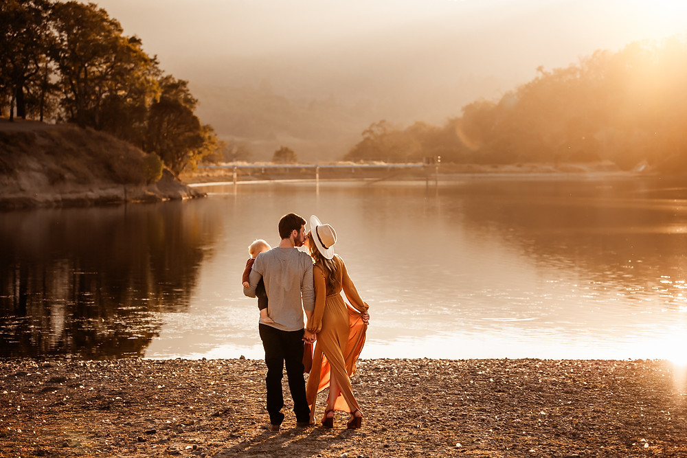 beautiful golden hour image in Sonoma County, wine country, mom and dad looking at sunset kissing each other,  mom holding out her gold dress, rolling hills in the background