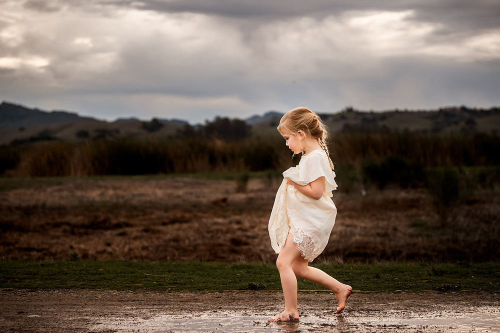 girl in long white dress from Joyfolie clothing, walking through a puddle, sunset photo session, portraiture, family photographer for Sonoma County, Diana Jex Photography