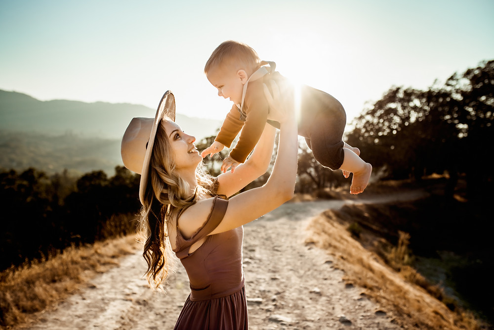 Beautiful mom holding up her toddler sun, sun shining in the background, golden hour, Sonoma family photographer