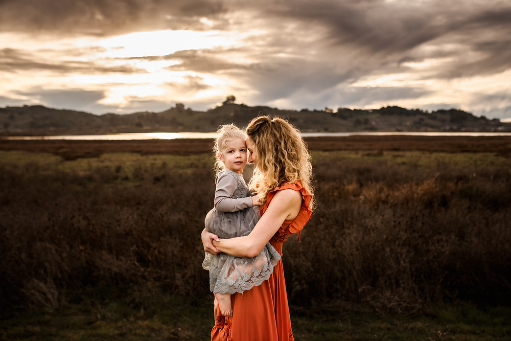 mother holding her daughter and cuddling up with her while her baby girl looks at the camera, daughter in blue dress from amazon, mom in long burnt orange dress from baltic born clothing, sunset with mountains in the background, golden hour, motherhood, family photographer for Sonoma County, Diana Jex Photography