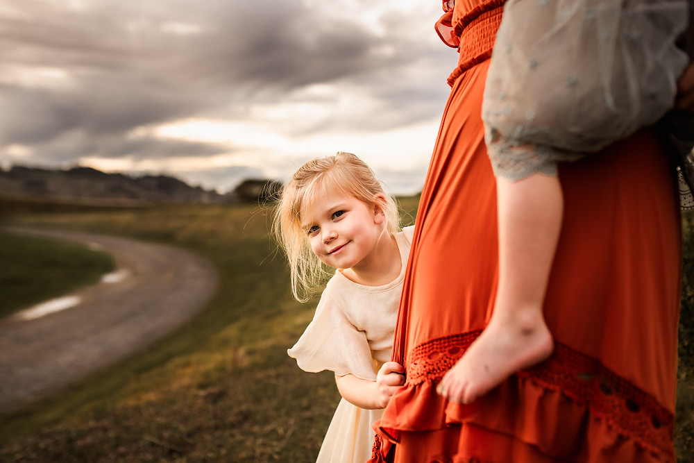 little girl playing peek a boo behind her mother's dress, sunset photo session in Sonoma County, family photographer for Sonoma County, Diana Jex Photography