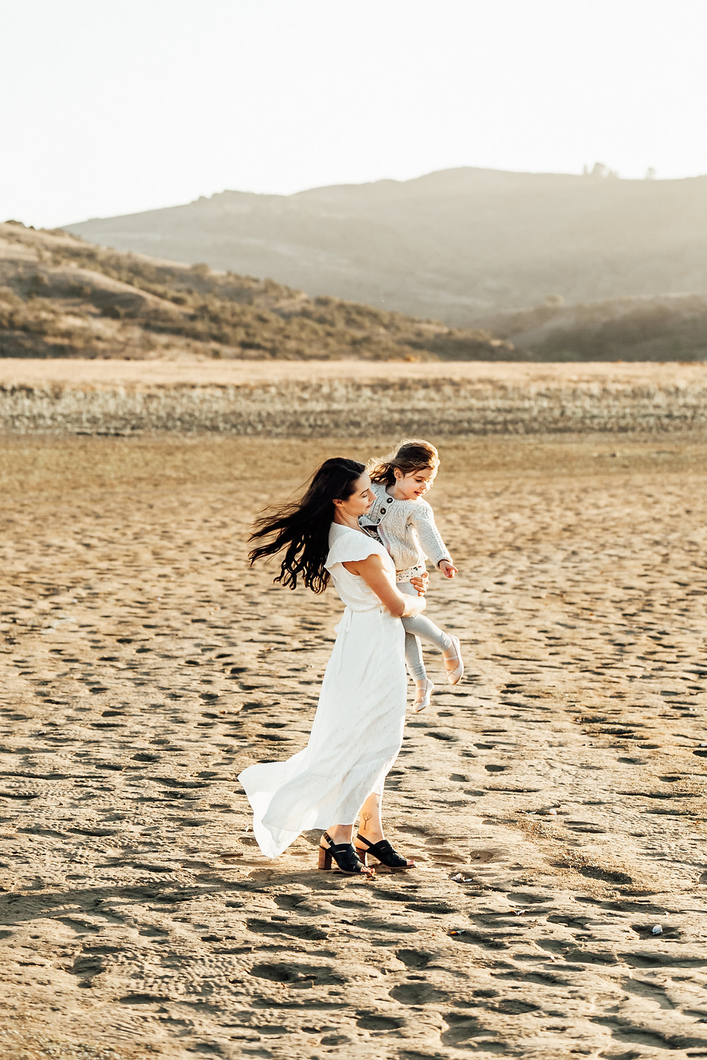 mom in long white maxi dress holding baby girl, wind and breeze in hair and dress, textured ground, sunset, motherhood family photographer Napa Novato Northern California Sonoma Diana Jex
