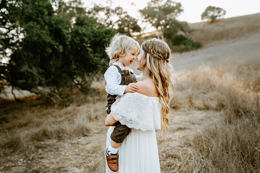laughing toddler boy snuggled in with pregnant mother, fall hills in the background, sunset photo session in Petaluma