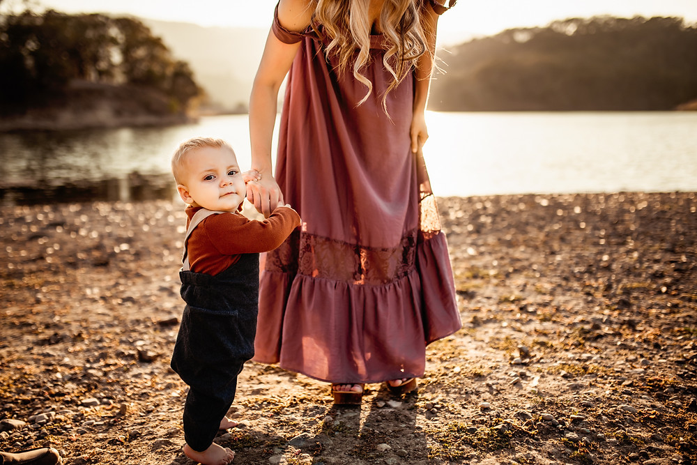 Gorgeous detail shot of mom holding her son's hands, backlight, golden hour, water and lake in background, rolling hills