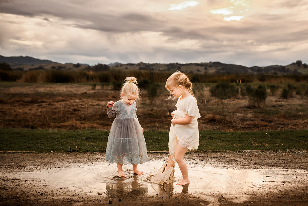 Sisters splashing in puddles together during a golden hour photo session in petaluma, family photographer for Sonoma County, Diana Jex Photography