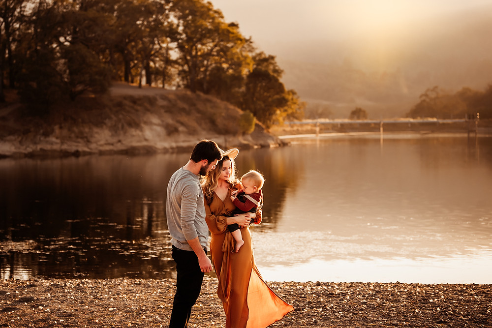 golden hour photograph in wine country, water in background, mom with flowy maxi dress, holding son, dad looking at son, rolling hills