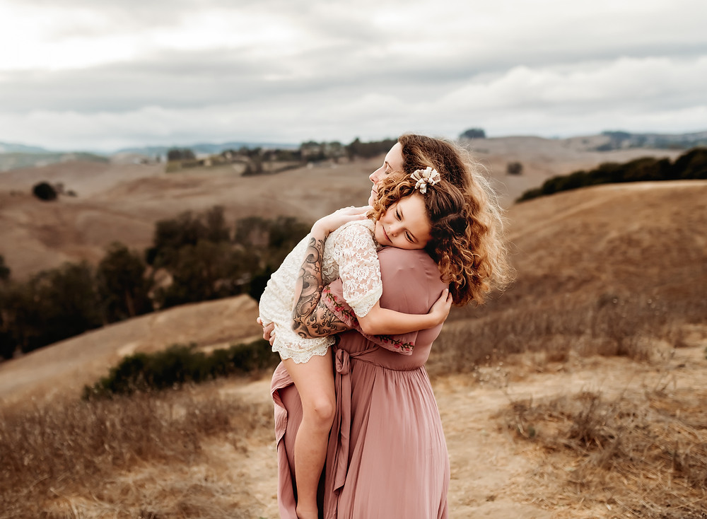 beautiful photo of daughter being held up by her expecting mom, little girl hugging her mom, looking over her shoulder, mom looking strong and beautiful, sunset in background, rolling hills, Sonoma County, petaluma maternity photographer Diana jex