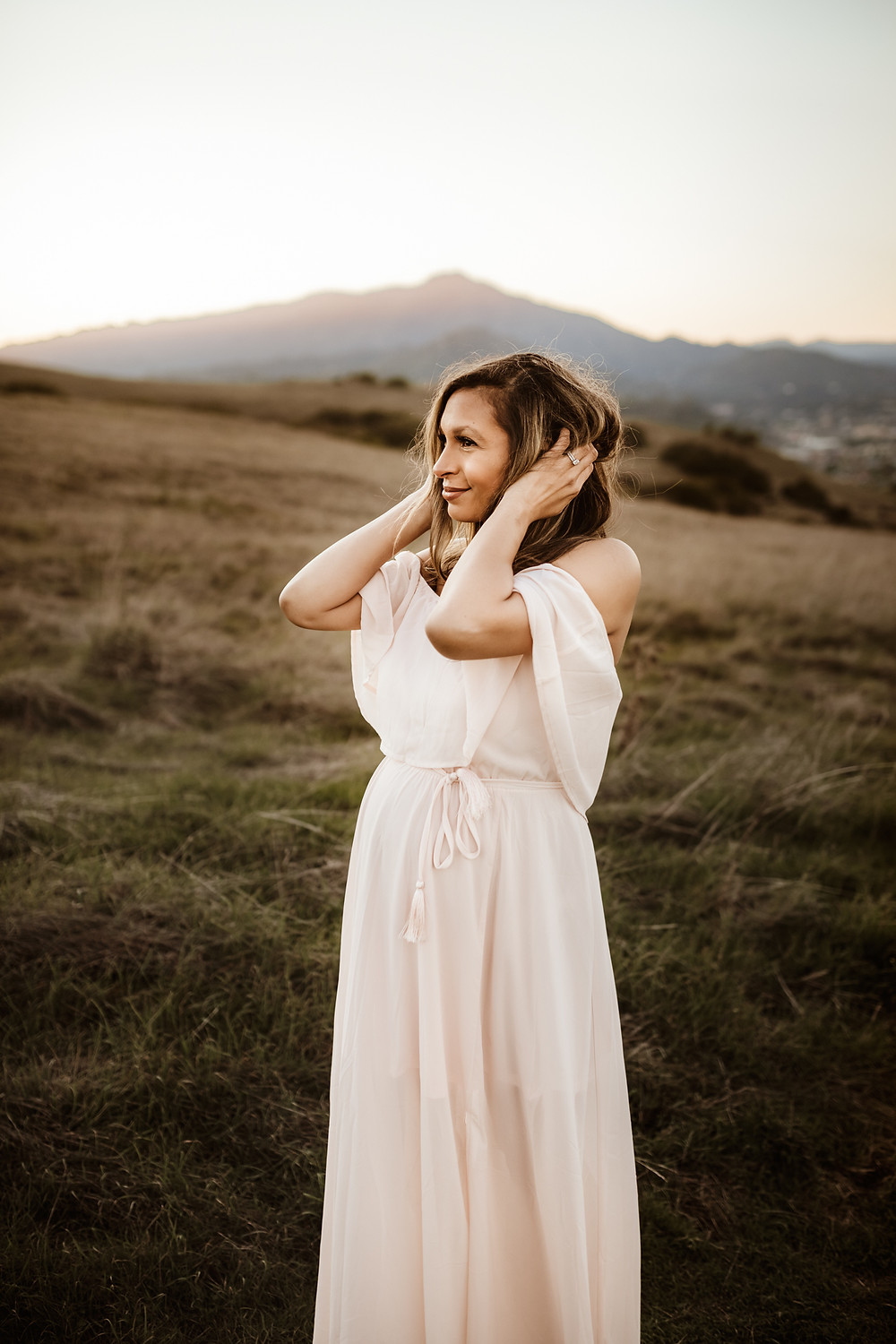 Portrait of pregnant mother during golden hour maternity photo session in Tiburon, looking off into the distance while running her fingers through her hair, petaluma family photography, Petaluma family photographer, Sonoma County family photographer, Marin County family photographer