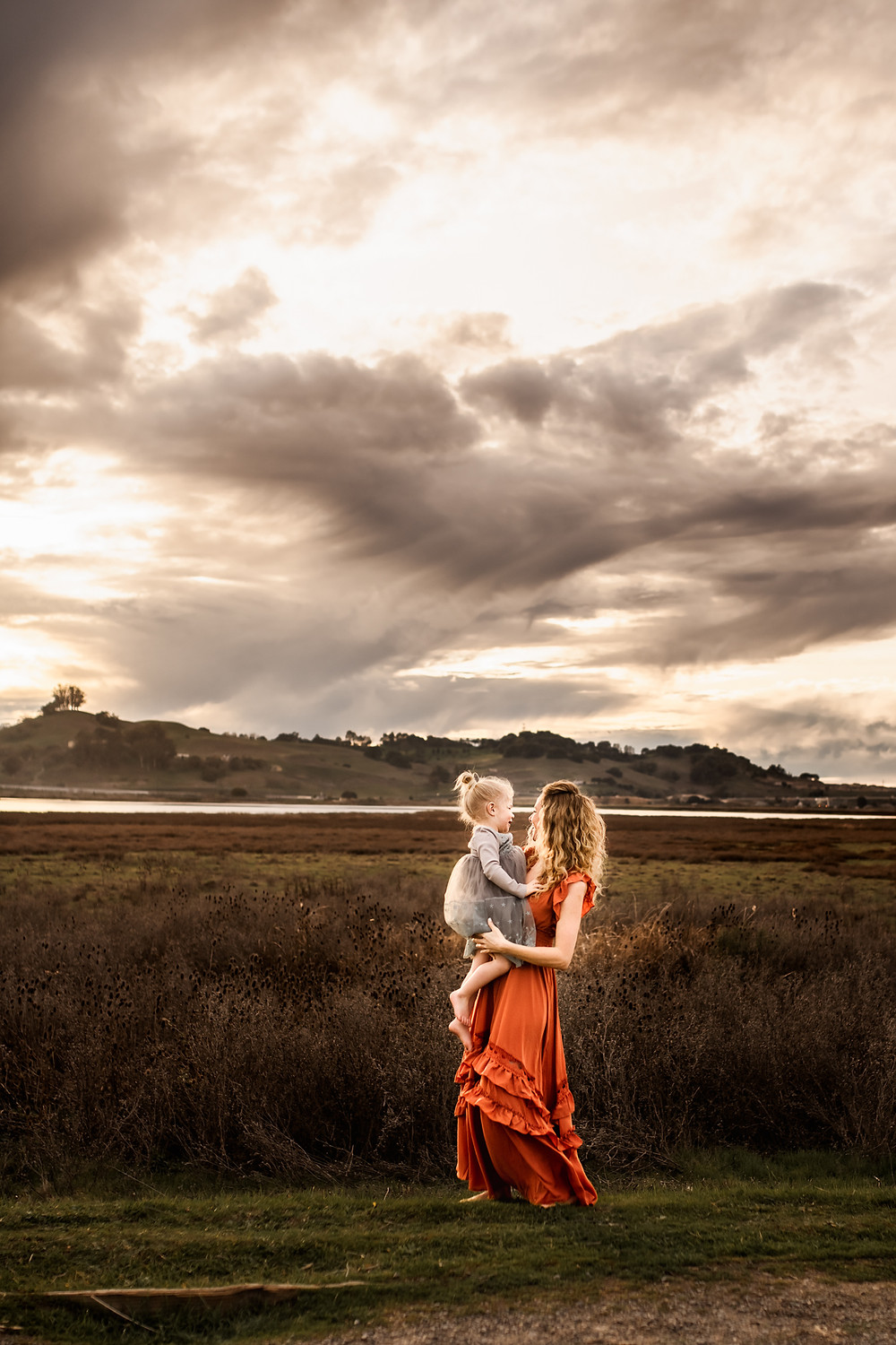 mother holding her baby girl with dramatic clouds and mountains in the background, mother and daughter spinning together, family photographer for Sonoma County, Diana Jex Photography