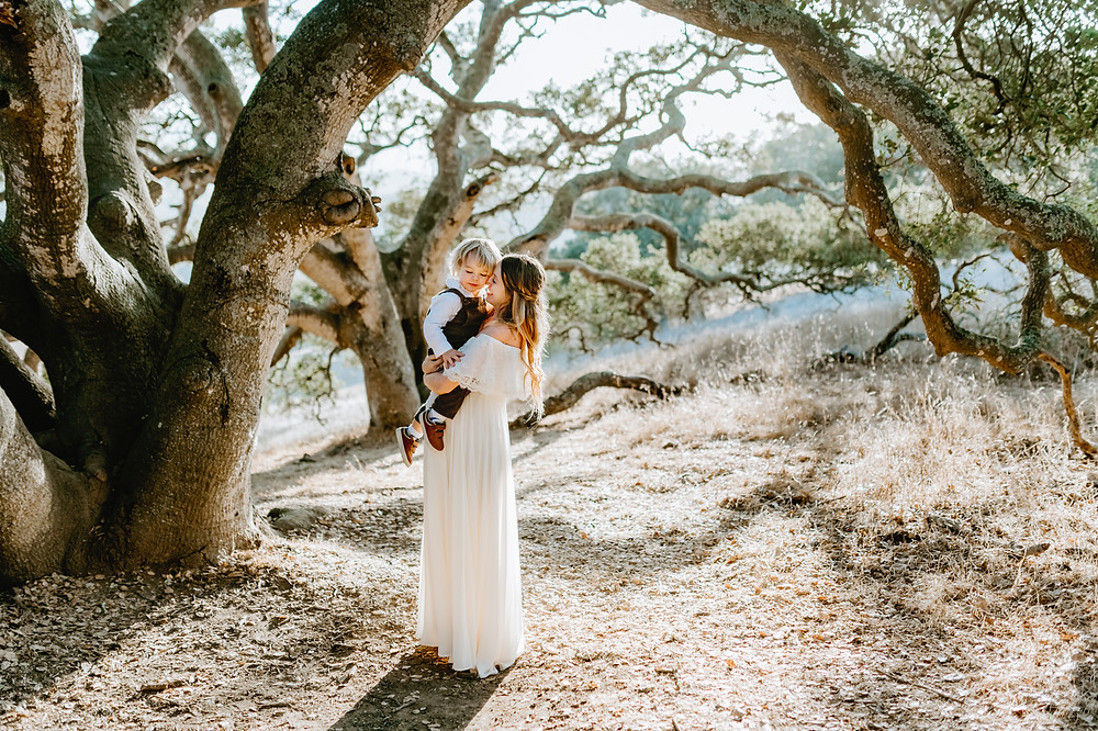 pregnant mom in white maxi dress holding her toddler boy under a tree canopy in Sonoma County California