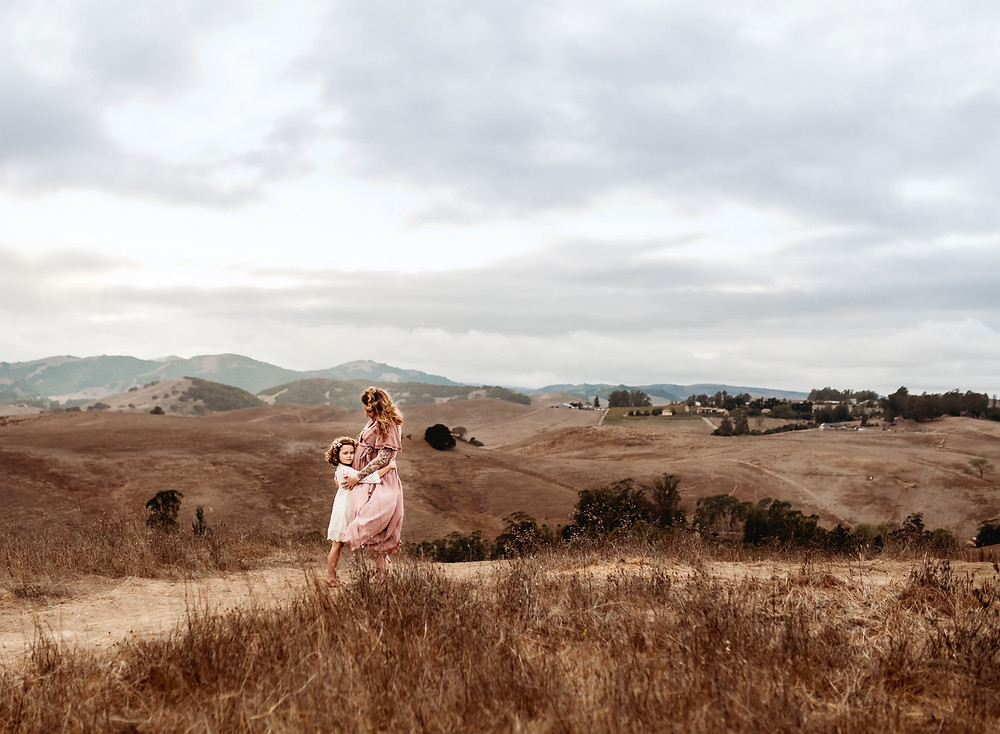 Little girl hugging her pregnant mom, embracing each other at the top of a hill in Sonoma County, fall maternity photo session, santa rosa maternity photographer, Diana Jex, maternity photography