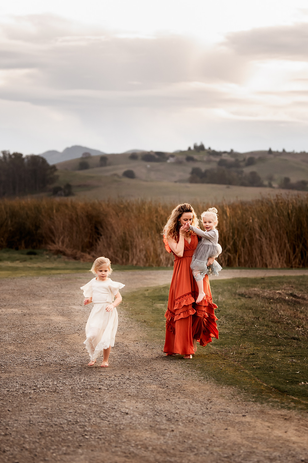 a mother and her daughters walking on a path, open space preserve in petaluma, mom is holding her daughter kissing her hand while her other daughter is walking ahead, golden hour motherhood session, family photographer for Sonoma County, Diana Jex Photography