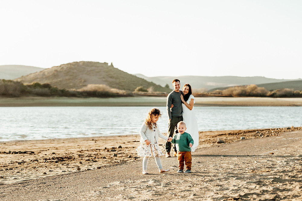 mom and dad embracing each other in background, siblings daughter and son playing, holding hands, lake, water, sunset, Sonoma County family photographer, Diana Jex , family of four, mom in long maxi white dress