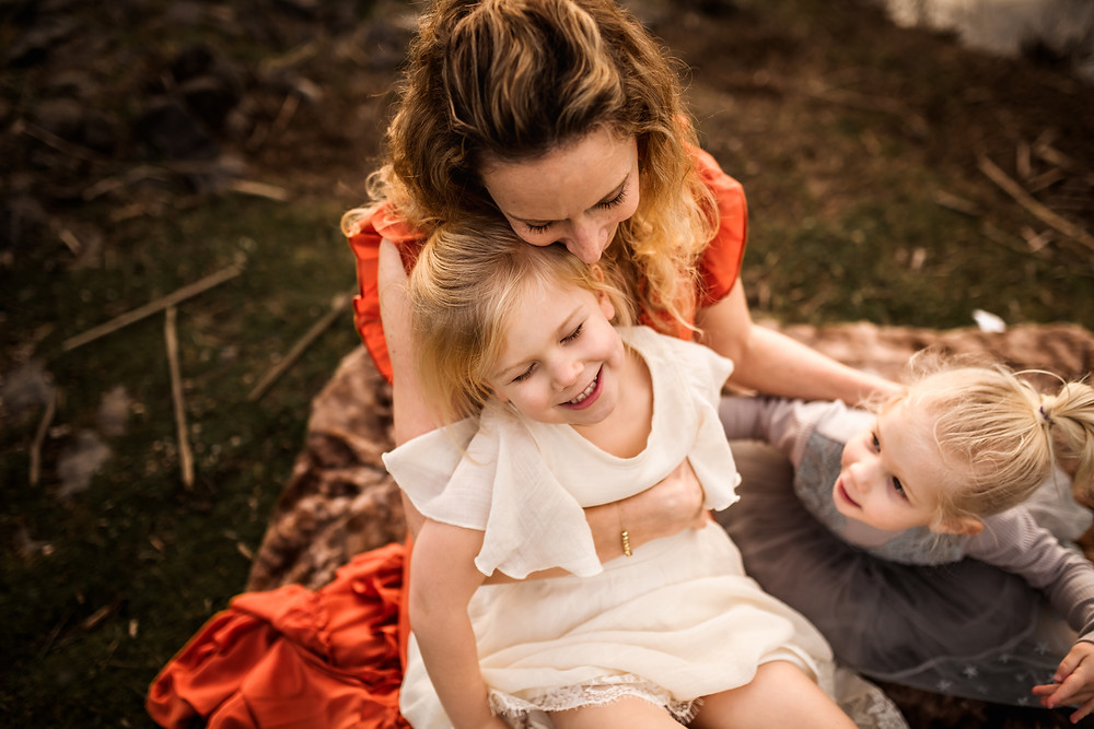 mom cuddling with her two daughters on a faux fur brown blanket, pond in background, big sister is laughing and little sister is curious, family photographer for Sonoma County, Diana Jex Photography