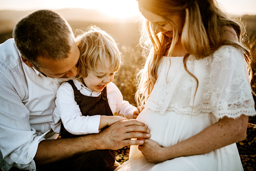 family of three sitting together outside with sunset behind them, little boy dressed in Brown overalls tickling mom's belly