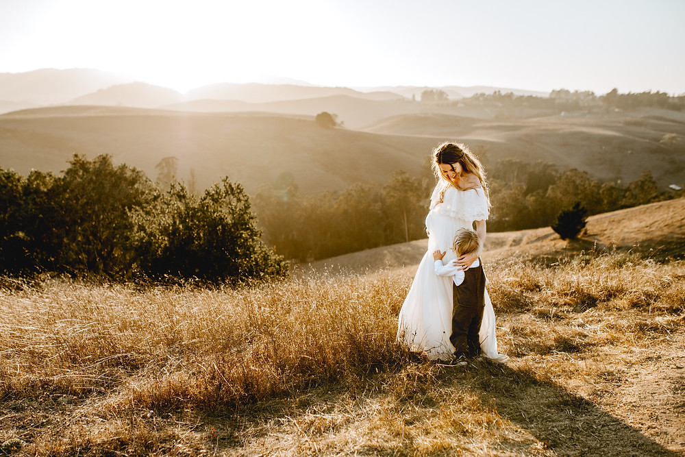 beautiful mother and son embracing each other, golden hour and sunset with rolling hills in background, pregnant mother in maternity dress, baby boy in brown overalls with a white shirt, Sonoma County maternity photographer, Diana Jex