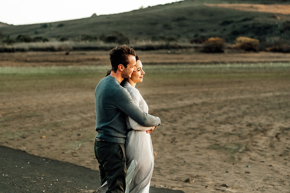 beautiful couple looking off into the sunset while holding each other and hugging, mom in white long maxi dress with long cardigan, dad in green sweater, golden hour, couples photographer, Sonoma county family photographer , petaluma family photographer, Diana Jex Photography