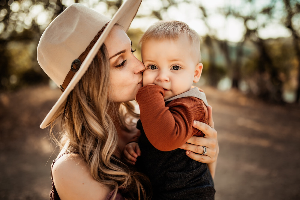 Mom kissing and holding close her baby boy, golden hour photography in Sonoma County