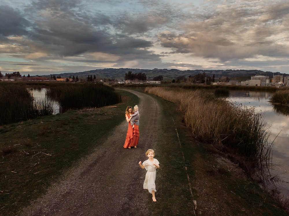 drone photograph of daughter running towards camera with her mom and baby sister in the background, walking on a trail, drone photography, sunset, dramatic clouds in the sky, water on both sides of the path, family photographer for Sonoma County, Diana Jex Photography