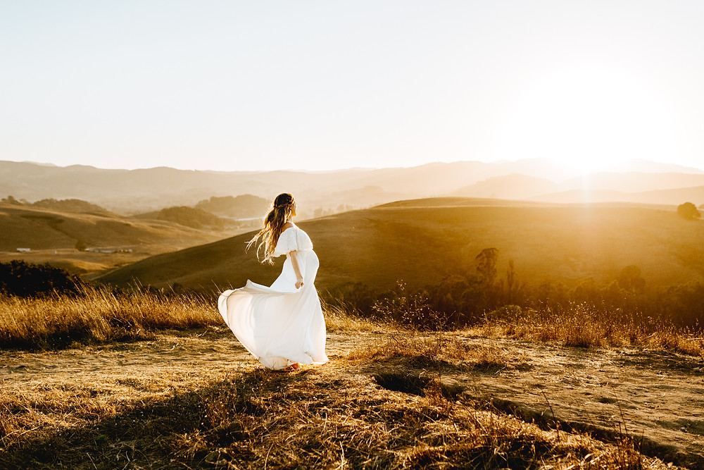 pregnant mother holding dress, flying in the wind, golden hour photography session, white dress, sunset, Sonoma County
