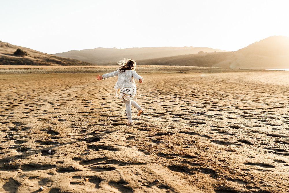 little girl dancing, textured landscape and ground, girl in white pattern dress and sweater, sunset, sibling, family photography Sonoma County, Petaluma Novato Diana Jex