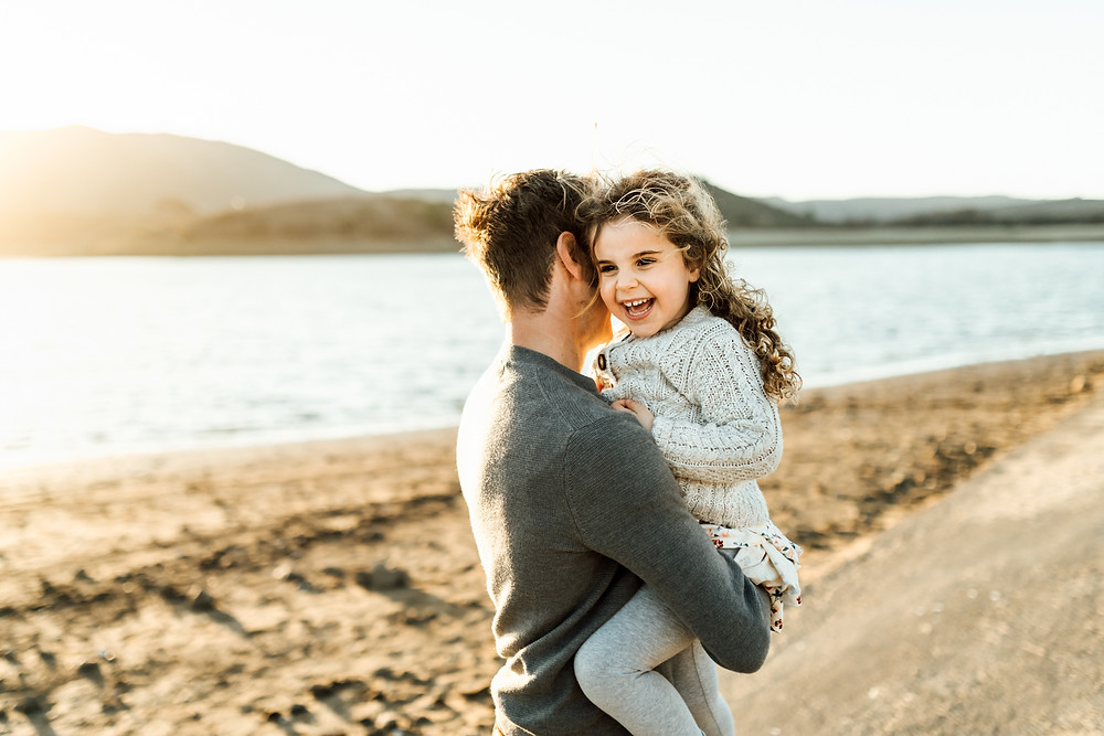 Little girl laughing and smiling while dad is holding her up, California family photographer, Diana Jex Marin county, sonoma, lake water, sunset, light, golden hour photography