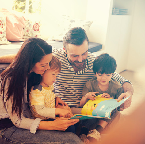 family-sitting-on-floor-reading-story-at