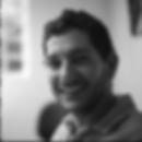 Foto estilo 3x4 de Rodrigo Sabie em preto e branco, ele esta de com camiseta de gola de cor clara sorrindo e cabelo curto