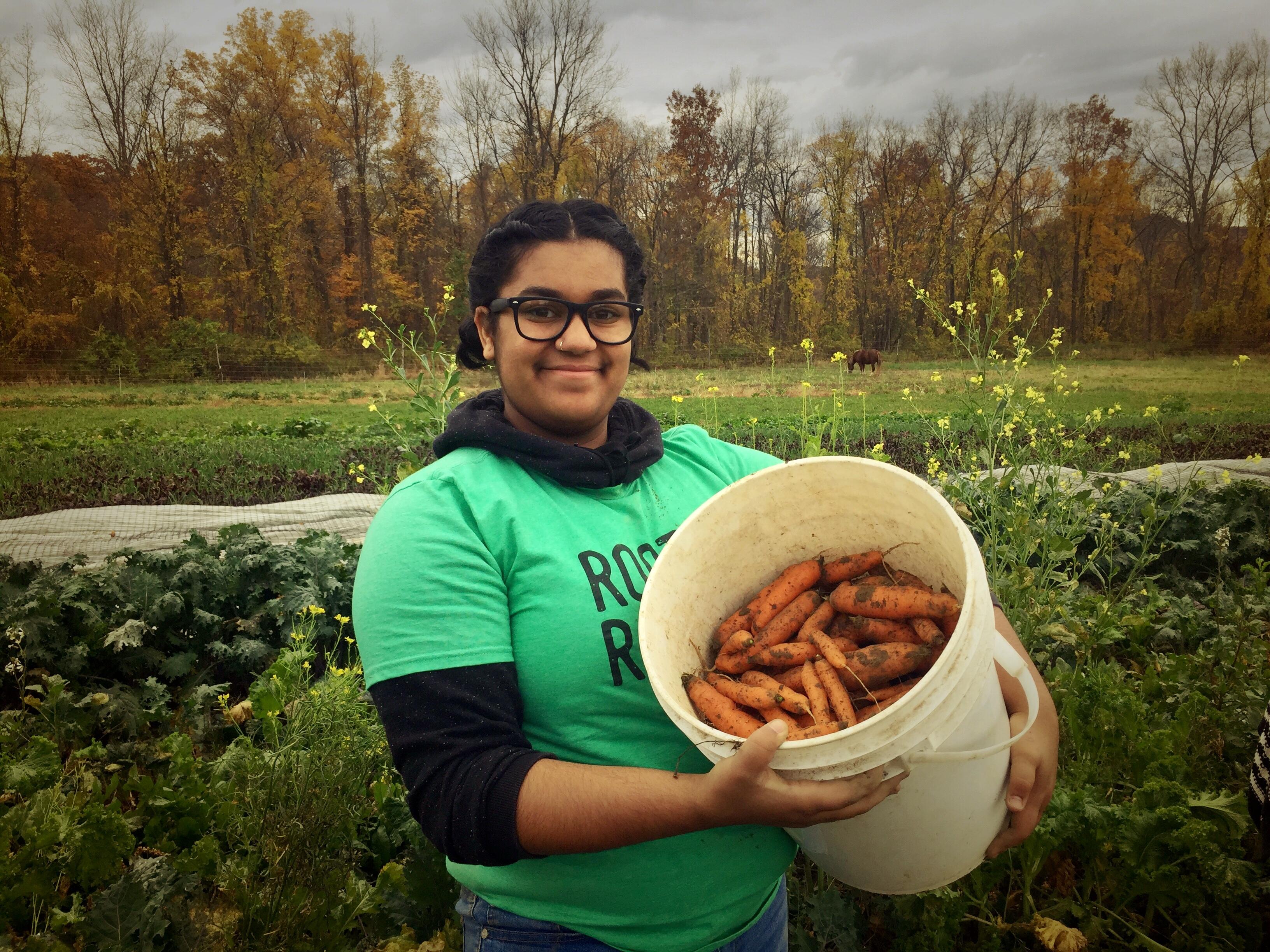 Shelbi displays her carrot harvest.