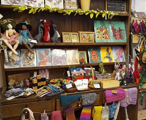 Welsh dresser crammed with goods: felt dragons - printed cards - cloth dolls - socks - organic soaps