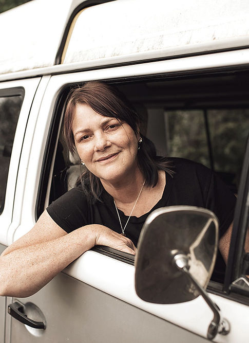 Artist Hawys Vickery smiling and leaning out of the window of her VW camper van.