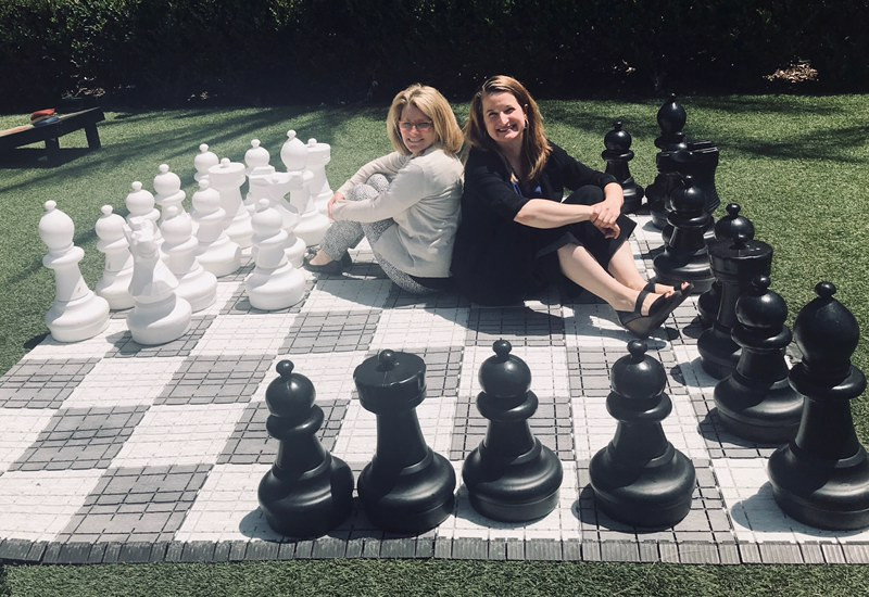 Catina O'Leary and Amy Waterman sit back to back on a life-size chess board, surrounded by large chess pieces