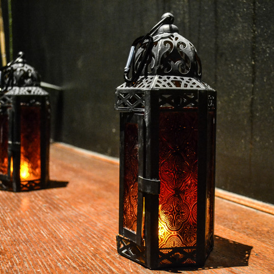 Candle lanterns line the bar top at a private themed party
