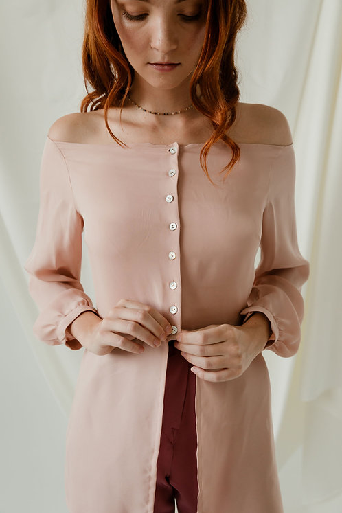Woman buttoning up an off the shoulder long sleeve light pink blouse.