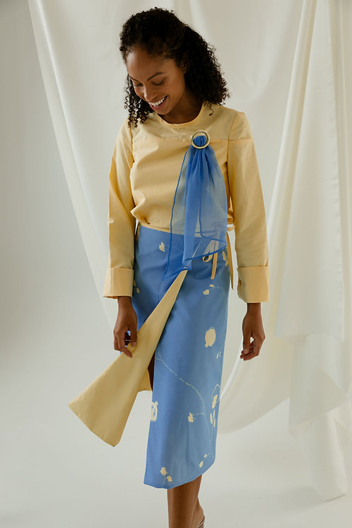 Woman wearing made to measure reversible blue and yellow floral wrap skirt  and yellow blouse with brooch.